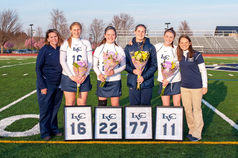 Women holding flowers posing on football field
